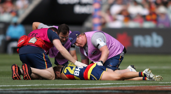 An Adelaide Crows AFLW player lies on the ground after being concussed.