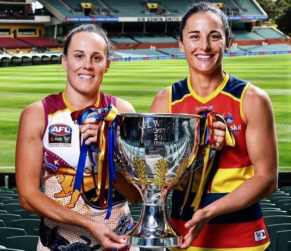 Two AFLW players hold the premiership trophy.