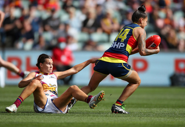An Adelaide Crows AFLw players attempts to get away from a Brisbane Lions opponent.