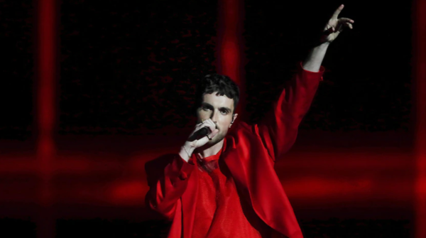 A performer in a red outfit gestures while singing at a Eurovision Song Contest semi-final.