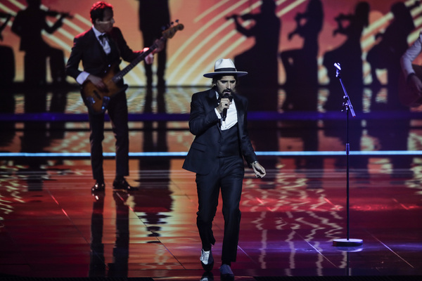 A man walks down a stage wearing a suit with a hat on, as he sings, with a band seen behind him.