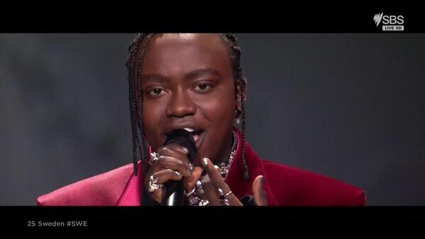 Tusse looks to the camera while singing. His hair is braided and he has many rings on his hands as well as silver nail polish.