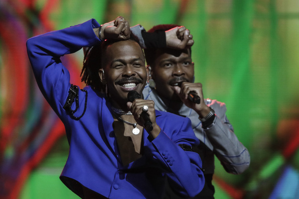 A man sings on a stage with a backing singer behind him. Both hold their fists to their heads and smile, against a multicoloured background.
