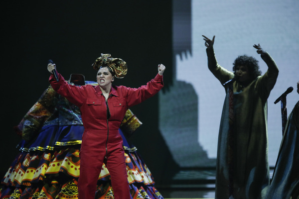 A woman stands on a stage pulling a fierce face with both hands in the air. She wears a red boilersuit and her hair is wrapped.