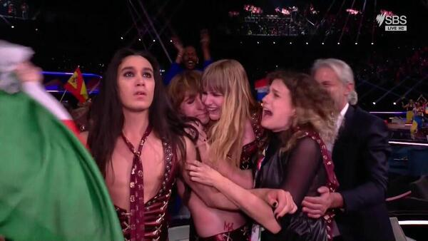 Performers from Italy's Eurovision act hug each other as they process the voting results.