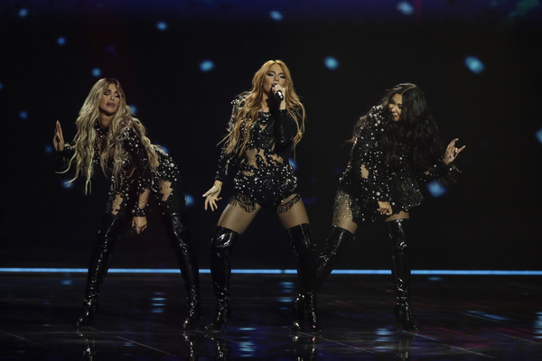 A lead singer in a dark dress performs while her bandmates dance beside her during a Eurovision semi-final.