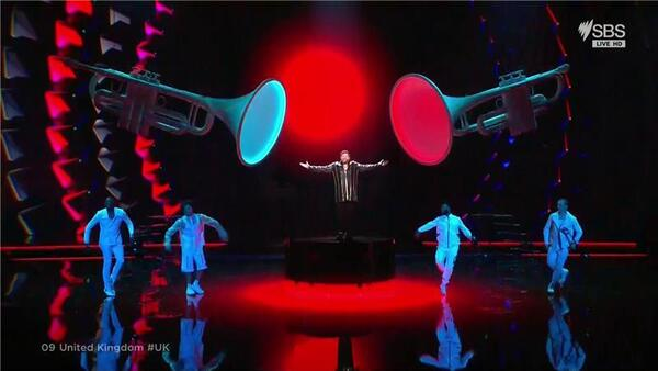 A man sings on stage between two giant trumpets
