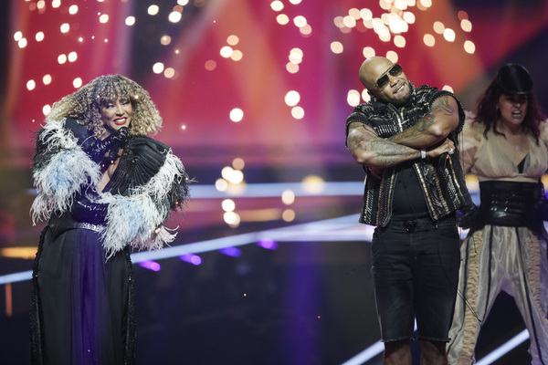 A woman stands in black with a feathered bolero jacket on a stage next to a man wearing a bedazzled vest. The backdrop is red.