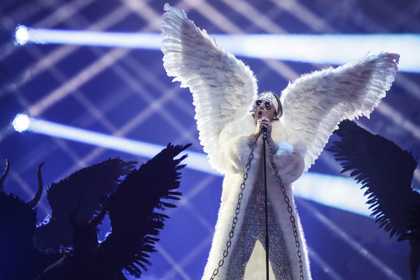 A man wearing a white headband and angel's wings stands at the microphone and sings while dark figures surround him on either side.
