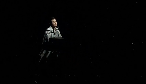 Duncan Laurence sits at a piano with a black, starry backdrop behind him. He wears a light jacket.