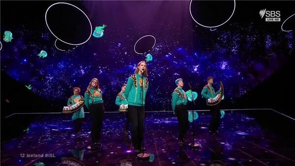 A band wearing kitschy green sweaters move on stage as video game characters are seen on the screen behind them.