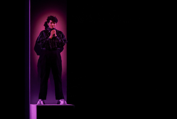 A man stands on a small platform with a white column behind him, bathed in pink and purple light. He wears a dark sparkly shirt and black pants and is deep in emotion.