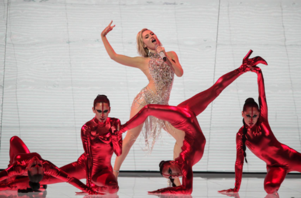 A singer performs on stage in white, surrounded by backing dancers clad in red.