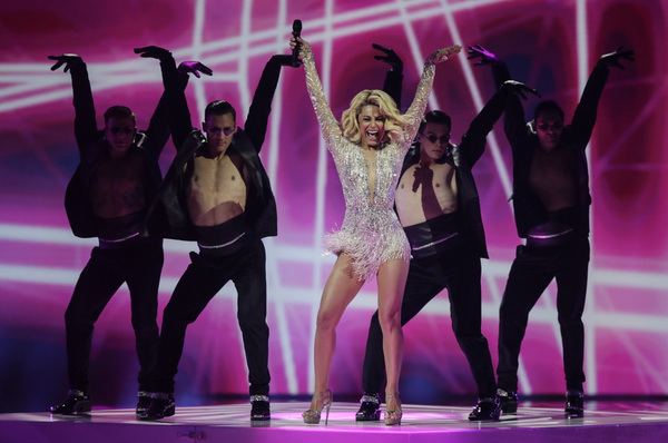 A performer in a silver dress puts her hands in the air as her barechested backing dancers do the same.