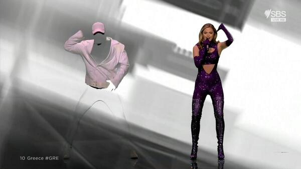 A woman in a purple glittery bodysuit stands next to a man wearing a green screen suit and a white jacket and cap on top.