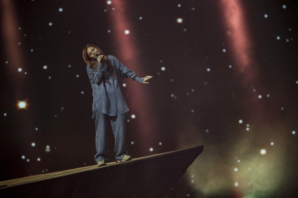 A woman performs standing on an imaginary rock on stage during Eurovision.