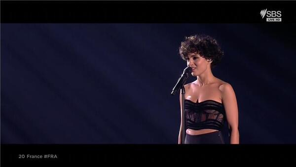 A French woman stands on stage with a dark background and sings.