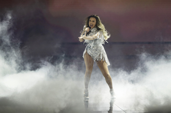 A female singer is surrounded by dry ice performs on stage in a silver dress during a Eurovision rehearsal.