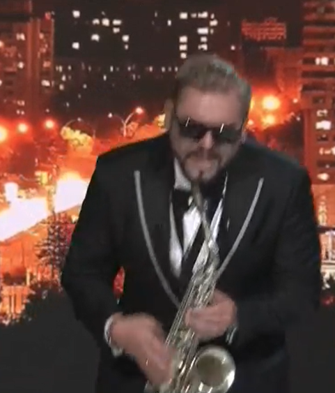 A man holds a saxophone and bends over while playing it, wearing a suit.