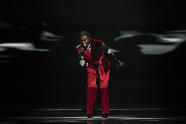 A man stands on a stage wearing a red satin sleeveless suit with black bedazzled gloves.