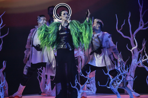 A lead singer wearing a green jacket has a glowing disc behind her head and a group of backing dancers with fake trees in the background.