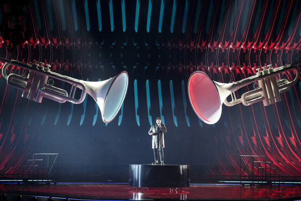 A man stands on a Eurovision platform singing, surrounded on either side by two massive trumpets.