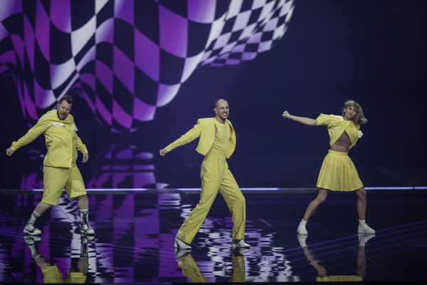 Three people dance on a purple stage with a checkerboard behind them. They're all wearing yellow.