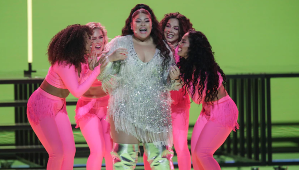 Destiny stands in a sequin and tasselled dress surrounded by four other women in hot pink. The set behind is green.
