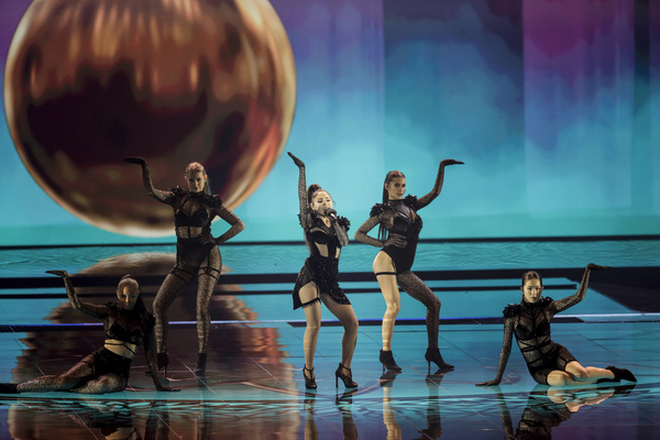 Five women stand on a stage posing with one hand up. Behind them is a huge metallic sphere. The women in centre holds a mic and is singing. They all wear black.