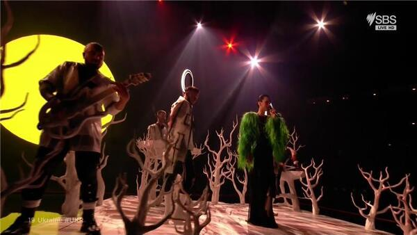 A band on stage amid fake white trees with a sun behind them.