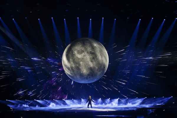 A man stands on a Eurovision stage singing, with a huge moon behind him.
