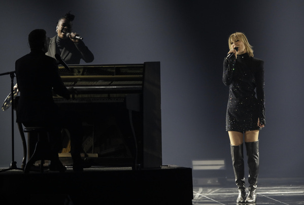 A woman stands in a black dress next to a man who is sat at the piano, with another person stood behind him.