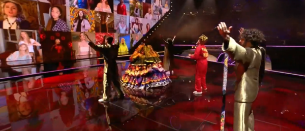 Manizha turns around and looks at a screen filled with Russian women singing. She's surrounded by other performers on stage.