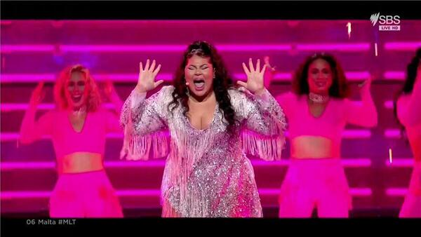 A female singer in a silver dress singing a big note with her hands raised as dancers move in the background.