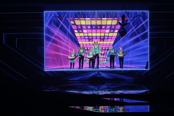 A video of a band clad in similar green jumpers plays on screen with an empty stage in the foreground.