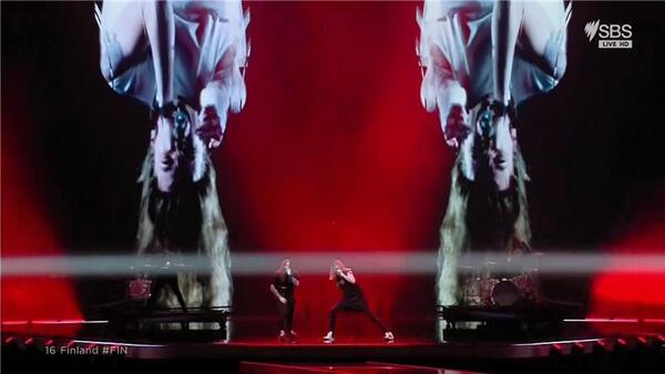 Two metal guys rock on stage with a red background on the big screen and a couple of upside-down faces.