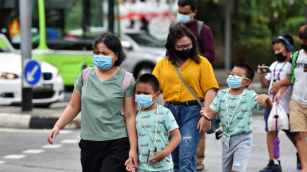 People wearing face masks cross a road, with several children in hand.
