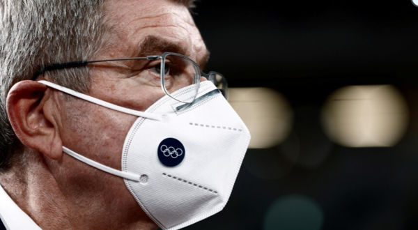 man wearing glasses and an Olympic branded face mask stares to the right.