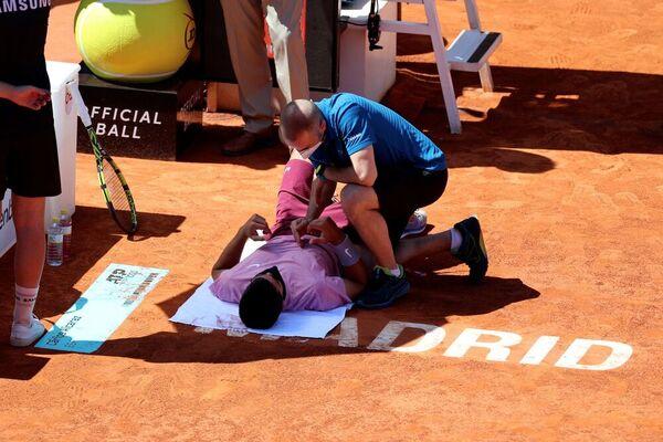 Carlos Alcaraz, atendido por el fisio tras sentir un dolor abdominal tras estirarse hacia el cielo a por una pelota FOTO: EFE