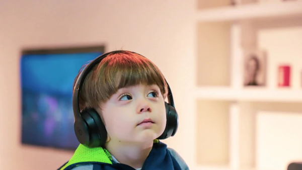 A child sits with headphones on