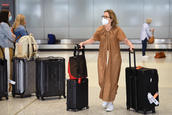 A woman with bags at an airport baggage carosel