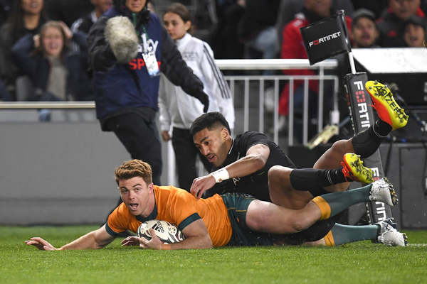 A Wallabies winger holds the ball with his left hand as he scores a try against the All Blacks.