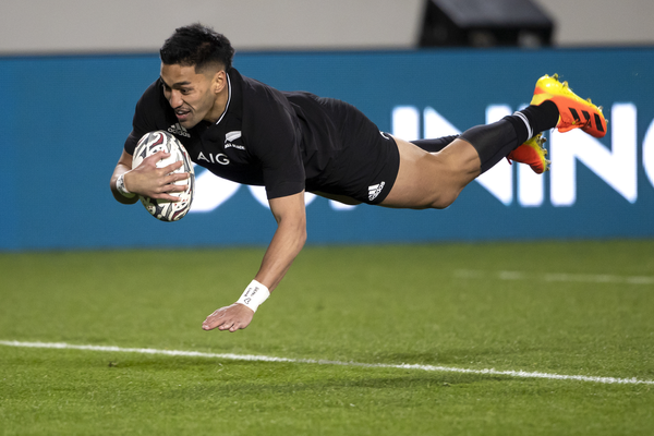 A New Zealand All Blacks try dives over to score a try.