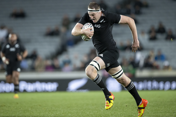 An All Blacks lock holds the ball with his right hand as he runs against the Wallabies.