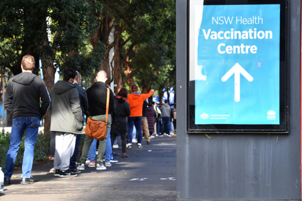 A sign points towards a vaccination clinic. A line of people extends past it.