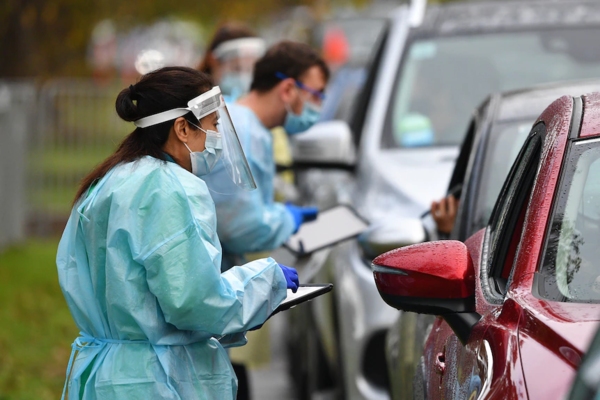 A line of health workers in PPE with clipboards speak to people through car windows