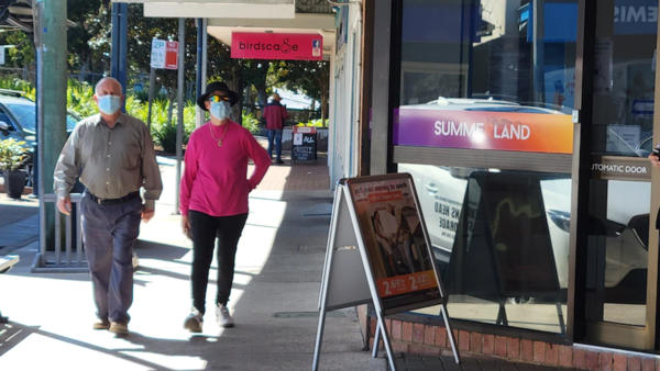 A masked couple walk by a strip of shops