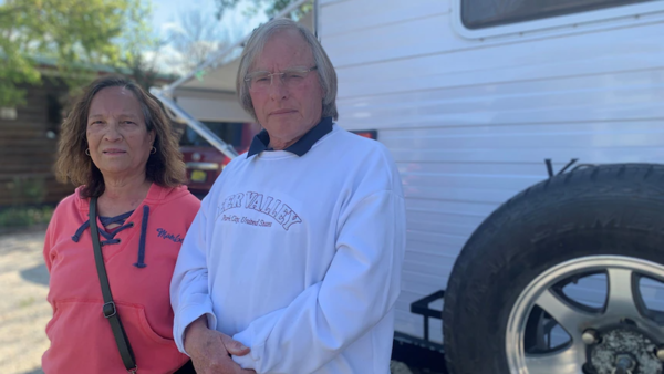 A man and a woman stand next to one another out the front of a caravan
