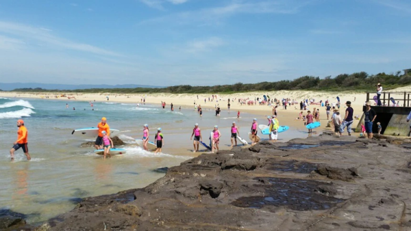 A crowded beach. Closest to the camera, a group of nippers enter the water