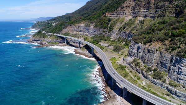 An aerial photo of a road winding along the coastline